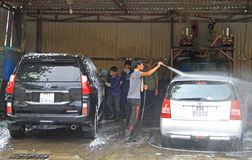 Serviceman is washing a car Royalty Free Stock Photos