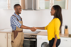 Serviceman And Woman Handshaking. Young Serviceman And Woman Handshaking In Kitchen Royalty Free Stock Photo