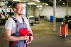 Serviceman in a workshop. Cheerful serviceman in a car workshop stock photo