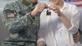 Serviceman and young wife holding house key, military service reward, purchase. Stock footage stock video