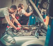 Servicemen in a car workshop Stock Photo