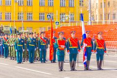 Servicemen of the guard of honor carry the banner of Victory and the Russian tricolor at the ceremonial march of the military par. Russia, Samara, May 2018 stock photography