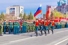 Servicemen of the guard of honor carry the banner of Victory and the Russian tricolor at the ceremonial march of the military par. Russia, Samara, May 2018 royalty free stock photo
