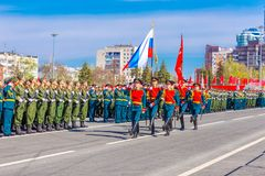 Servicemen of the guard of honor carry the banner of Victory and the Russian tricolor at the ceremonial march of the military par. Russia, Samara, May 2018 royalty free stock images