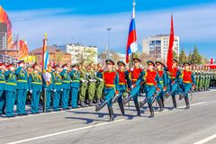 Servicemen of the guard of honor carry the banner of Victory and the Russian tricolor at the ceremonial march of the military par. Russia, Samara, May 2018 stock photo