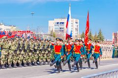 Servicemen of the guard of honor carry the banner of Victory and the Russian tricolor at the ceremonial march of the military para. Russia, Samara, May 2018 stock photo
