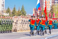 Servicemen of the guard of honor carry the banner of Victory and the Russian tricolor at the ceremonial march of the military para. Russia, Samara, May 2018 royalty free stock images