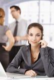Servicer do cliente novo usando auscultadores no escritório imagem de stock