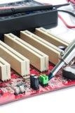 Servicer soldou a placa de circuito com um ferro de solda Fotografia de Stock Royalty Free