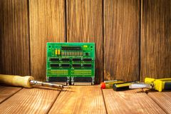 Services and repair of electronics, electronic boards. Wooden background. Services for the production of electronics and repair of electronic boards. Wooden royalty free stock images