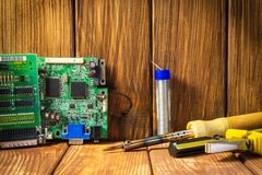 Services and repair of electronics, electronic boards. Wooden background. Services for the production of electronics and repair of electronic boards. Wooden stock image