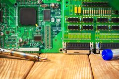 Services and repair of electronics, electronic boards. Wooden background. Services for the production of electronics and repair of electronic boards. Wooden stock photos