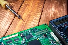 Services and repair of electronics, electronic boards. Wooden background. Services for the production of electronics and repair of electronic boards. Wooden royalty free stock image