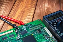 Services and repair of electronics, electronic boards. Wooden background. Services for the production of electronics and repair of electronic boards. Wooden stock photography