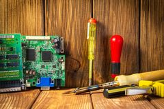 Services and repair of electronics, electronic boards. Wooden background. Services for the production of electronics and repair of electronic boards. Wooden stock photo