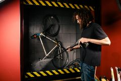 Services professional washing of a bicycle in the workshop. A young caucasian stylish man with long curly hair does a bicycle clea stock photography