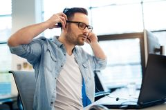Servicetelefonoperatör i hörlurar med mikrofon på arbetsplatsen Fotografering för Bildbyråer