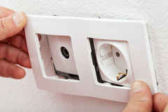 Servicing an electrical wall fixture Stock Photo