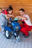 Servicing a small tiller machine. Man and boy servicing a small tiller machine - adding oil stock images