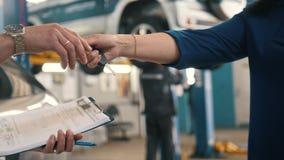 Servicio auto - la mujer da las llaves del coche para el mecánico almacen de metraje de vídeo