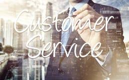 Servicio de atención al cliente de la escritura del hombre de negocios en la pantalla virtual detrás del th imagen de archivo libre de regalías
