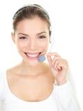 Servicio de atención al cliente sonriente del centro de atención telefónica de la mujer de las auriculares Imágenes de archivo libres de regalías
