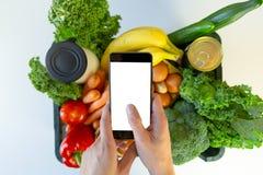 Servicio de entrega de la comida - smartphone de la tenencia de la mujer delante de la caja de ultramarinos fotos de archivo libres de regalías