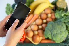 Servicio de entrega de la comida - smartphone de la tenencia de la mujer delante de la caja de ultramarinos imagenes de archivo