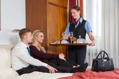 Servicio de habitación que trae la comida y el vino de los pares Fotografía de archivo