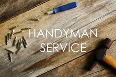 Servicio de la manitas escrito en fondo de madera con destornillador y el martillo fotografía de archivo