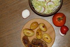 Servicio de la tabla con las patatas frescas Foto de archivo libre de regalías
