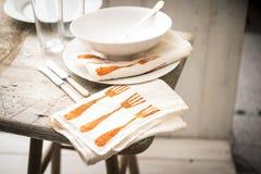 Servicio de mesa y servilletas modeladas en taburete de madera sobre el CCB de madera fotografía de archivo