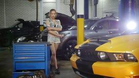 Servicio de reparación del coche La mujer joven camina alrededor del servise Cámara lenta almacen de video