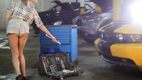 Servicio de reparación del coche La mujer joven en pequeños pantalones cortos camina a la caja de herramienta, dobla abajo y toma almacen de video