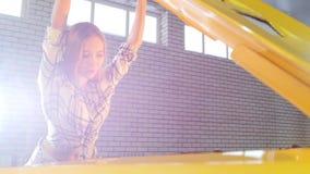 Servicio de reparación del coche Mujer atractiva joven que abre la capilla del coche y que parece interior metrajes
