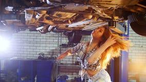 Servicio de reparación del coche Una elevación del coche Situación atractiva joven de la mujer debajo del coche Soluciona el prob almacen de video