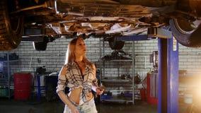 Servicio de reparación del coche Una elevación del coche Situación de la mujer joven debajo del coche y trabajo con una llave almacen de video