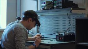 Servicio de reparación del dispositivo móvil del concepto El ingeniero desmonta el teléfono móvil almacen de metraje de vídeo