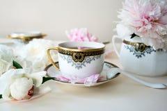 Servicio de té antiguo y peonías frescas, aún vida Imagen de archivo