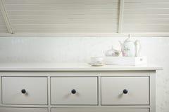 Servicio de té blanco en la cómoda blanca de manera operacional Comience una mañana con la taza de té o de café imágenes de archivo libres de regalías