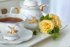 Servicio de té con té y flores Foto de archivo