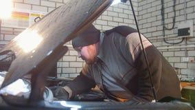 Servicio del coche El hombre grueso del mecánico comprueba el aceite almacen de video