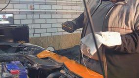 Servicio del coche El hombre grueso del mecánico comprueba el estado del aceite almacen de metraje de vídeo
