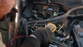 Servicio del coche El hombre grueso del mecánico comprueba el voltaje almacen de metraje de vídeo