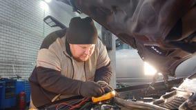 Servicio del coche El hombre grueso del mecánico comprueba el voltaje con un multímetro almacen de video