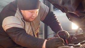 Servicio del coche El hombre grueso del mecánico del jengibre comprueba el voltaje con un multímetro metrajes