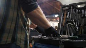 Servicio del coche Hombre del mecánico que busca una herramienta en el caso metrajes
