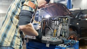 Servicio del coche Hombre del mecánico que elige una herramienta en el caso metrajes