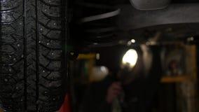 Servicio del coche - parte inferior del coche en una elevación en un taller 4K metrajes