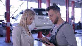 Servicio del coche, trabajador con la tableta a disposición que habla con un cliente femenino en el fondo del vehículo en la elev almacen de video